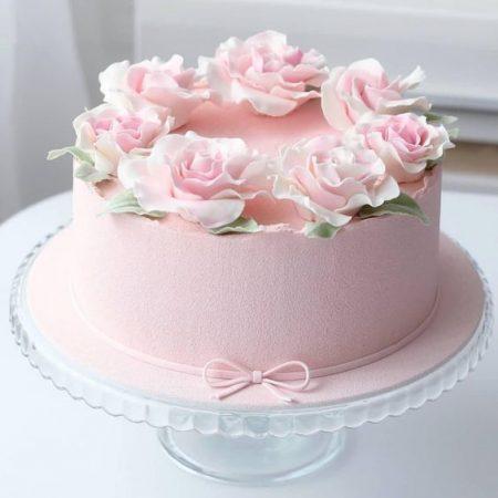 Торт цвета пудры с цветами и бантом